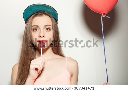 Beautiful hipster girl in cap is eating a lollipop with enjoyment. She is holding a red balloon and looking forward with joy. Isolated on background - stock photo