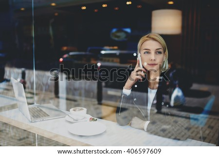 Beautiful hipster girl is phoning via smart phone, while is sitting at cafe table with laptop computer. Female student is calling via cell phone, while is resting after on-line learning via net-book - stock photo