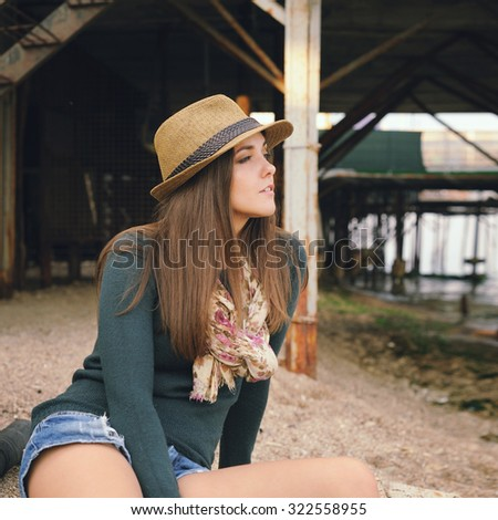 Beautiful hipster girl resting under the old pier on a sea beach, autumn outdoor. - stock photo