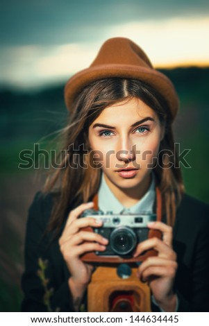 Beautiful hipster girl shooting with retro camera - stock photo