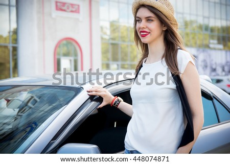 Beautiful hipster girl standing near her car ,wearing hat,jeans and sunglasses