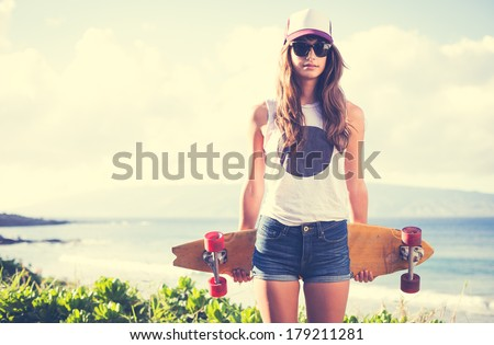 Beautiful hipster girl with skate board wearing sunglasses - stock photo