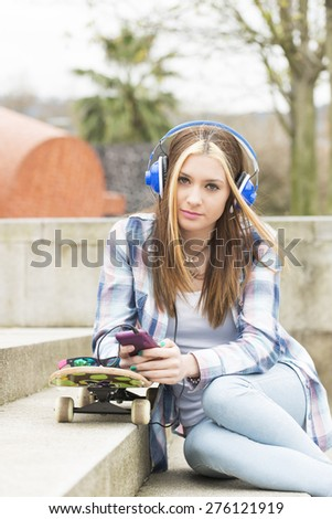 Beautiful hipster girl with smart phone and skateboard in the street, urban lifestyle concept. - stock photo