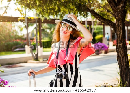 Beautiful hipster happy redhead woman traveler in the airport waiting area, with a suitcase and a camera in sunglasses, a hat, a bright fashionable clothes, summer style - stock photo