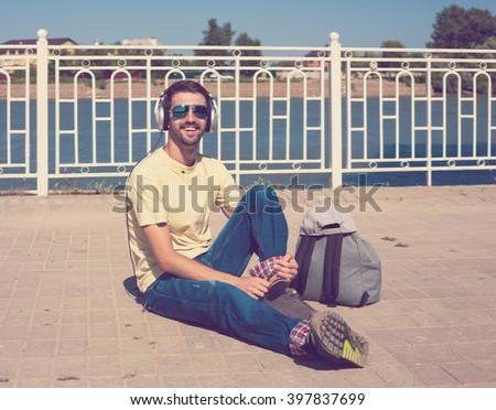 Beautiful hipster man, has smile face, yellow t-shirt, blue jeans, slim sport body, gray backpack, sunglasses, listen to music on headphones. Urban city portrait. Happy fun concept. - stock photo