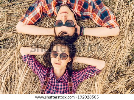Beautiful hipster style couple is lying on meadow - stock photo