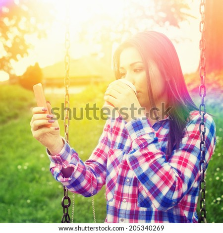 Beautiful hipster teenage girl with takeaway coffee and smartphone. Cute mixed race casual young woman taking a selfie in park sitting on a swing. Square format image. - stock photo