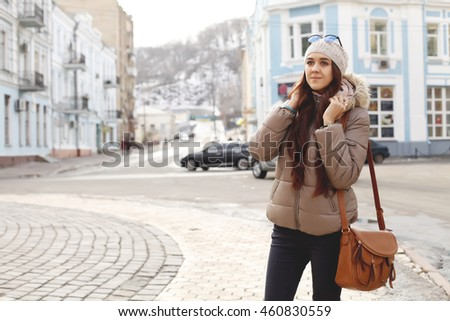 Beautiful hipster woman in red beanie hat in the winter park