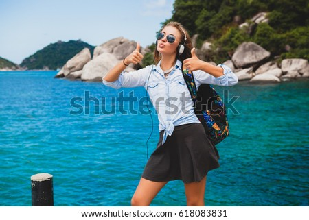 beautiful hipster woman traveling around world with backpack, smiling, happy, positive, listening music in headphones, blue tropical ocean background, thumbs up, sunglasses, sexy, summer vacation,