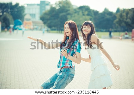 beautiful hipster young women sisters friends dancing listening music  in the city - stock photo