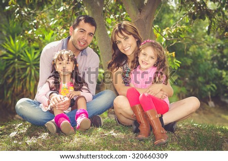 Beautiful hispanic family of four sitting outside on grass engaging in conversations while posing naturally and happily. - stock photo