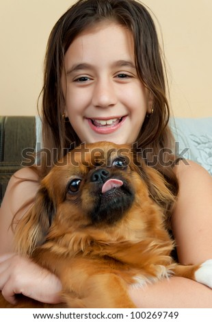 Beautiful hispanic girl carrying her small pekingese dog and smiling - stock photo