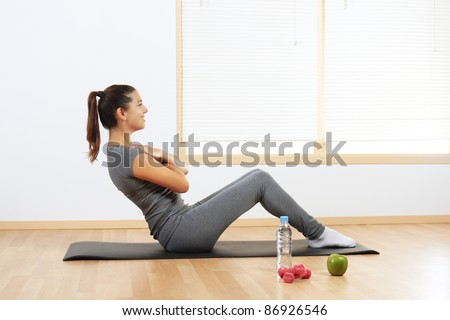 Beautiful Hispanic girl doing sport exercises at home