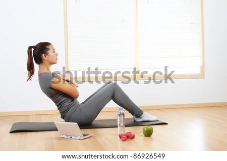 Beautiful Hispanic girl doing sport exercises at home - stock photo