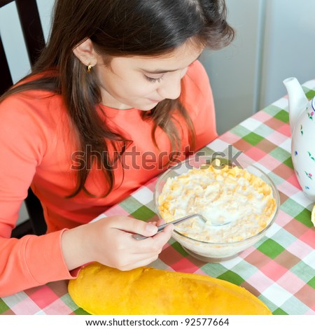 Beautiful hispanic girl eating breakfast on a bowl with milk and cereal - stock photo