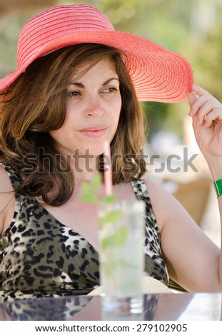 Beautiful Hispanic middle aged woman drinking her Mojito cocktail and wearing a pink straw hat while enjoying a sunny summer day. - stock photo