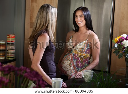 Beautiful Hispanic pregnant woman with her friend in the kitchen - stock photo