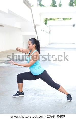 Beautiful hispanic sport woman demonstrating tai chi stance  'shuttle back and forth', outdoor. Concept of healthy lifestyle. - stock photo