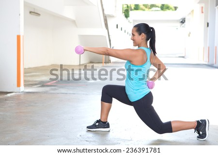 Beautiful hispanic sport woman doing lunges with two pink dumbbell, outdoor. - stock photo