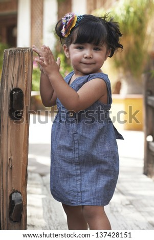 Beautiful Hispanic toddler girl playing at rustic garden park on sunny day. - stock photo