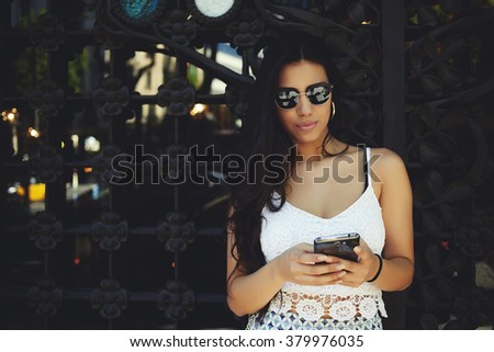 Beautiful Hispanic woman checking email via mobile phone while standing outdoors near copy space, charming female holding cell telephone in hands while waiting for friend outside in warm summer day - stock photo