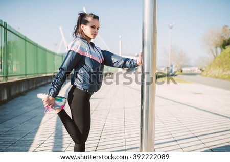 Beautiful hispanic woman doing stretching before running outdoors
