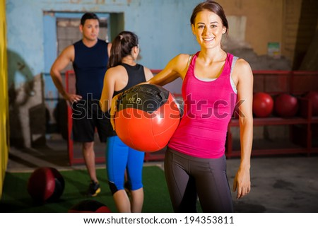 Beautiful Hispanic woman exercising with a medicine ball in a cross-training gym