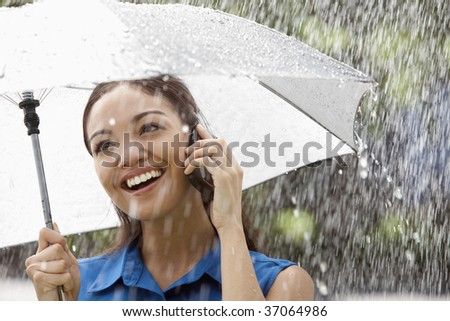 Beautiful Hispanic woman holding umbrella out in the rain talking on a cell phone - stock photo