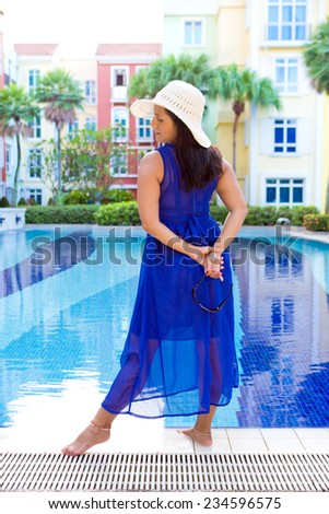 Beautiful hispanic woman in blue dress and sun hat standing by the edge of a swimming pool - stock photo