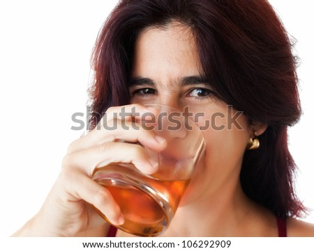 Beautiful hispanic woman in her thirties drinking whisky, rum or any other golden liquor isolated on white