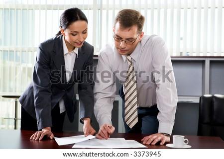 Beautiful Hispanic woman showing a document to her colleague - stock photo