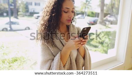 Beautiful hispanic woman texting on a cell phone. - stock photo