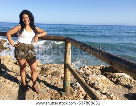 Beautiful hispanic woman with culy hair smiling at beach in front of the ocean in summer