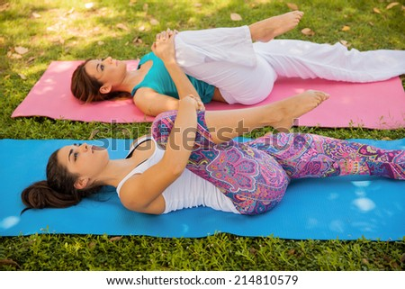 Beautiful Hispanic women doing some stretching at a park for their yoga practice - stock photo