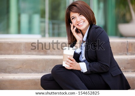 Beautiful Hispanic young business woman talking over the phone during her coffee break - stock photo