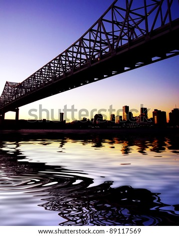 Beautiful historical Crescent City Connection Bridge in New Orleans Louisiana. Skyline, cityscape with reflection in water. - stock photo