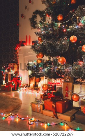Beautiful holdiay decorated Christmas tree with present boxes near fireplace in living room. Shining lights, balls and garland on fir tree. Winter holiday night magic. Design and decoration background