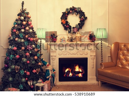 Beautiful holiday decorated room with Christmas tree, fireplace and gold armchair. Cozy winter scene. White interior with lights.