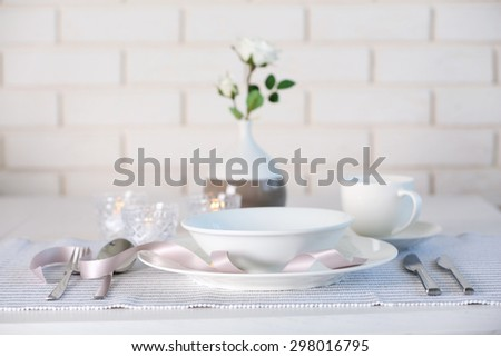 Beautiful holiday table setting in white and gray color - stock photo