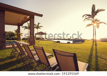 Beautiful Home Exterior Patio Deck and Lounge Chairs with Sunset View on Lawn - stock photo