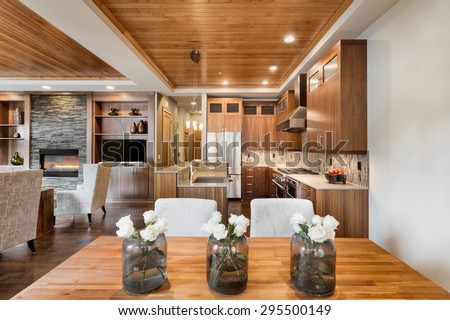 Beautiful home interior with open floor plan: includes dining room, kitchen, and living room with dining room table, flowers, wood strip tray ceiling, cabinets, hardwood floors, and fireplace - stock photo