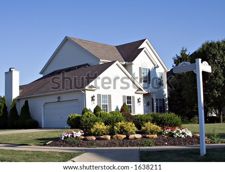Beautiful home on the corner of the street.  Street signs are blank. - stock photo