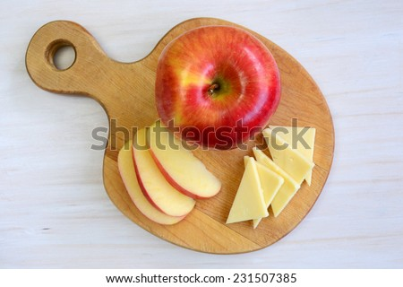 Beautiful honeycrisp apple on unique apple shaped cutting board on rustic white background - stock photo