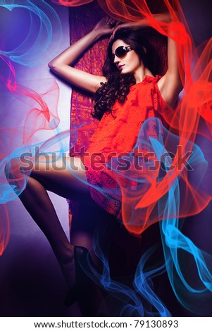 beautiful hot woman in sunglasses and red dress around fabric - stock photo