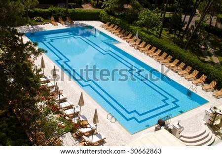 Beautiful hotel swimming pool in a garden - stock photo