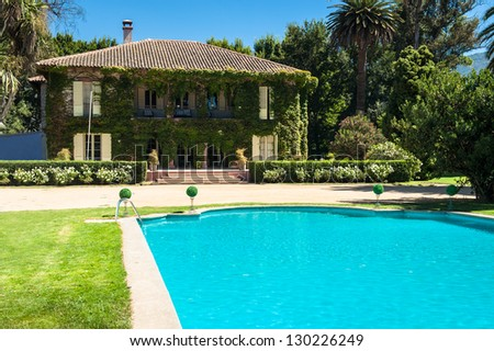 Beautiful house and backyard with a swimming pool in the foreground - stock photo