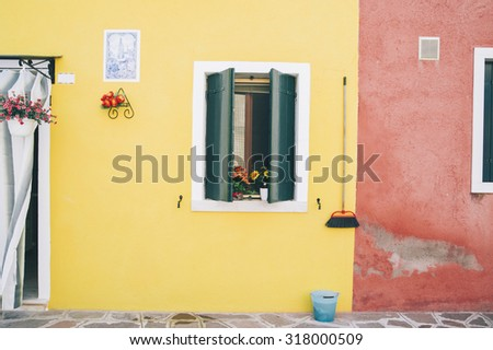 Beautiful house facade on Burano island, north Italy. Colorful Yellow house wall with a door and windows