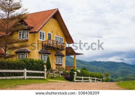 beautiful house on a background of mountains - stock photo