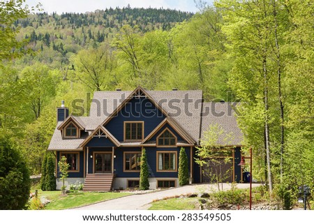 Beautiful house or cottage in the hills spring time - stock photo