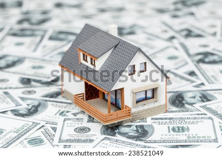 Beautiful house standing on dollar bills. Home expenses or investing concept. - stock photo